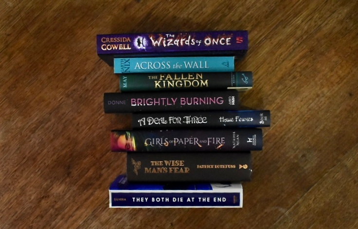 A 'spell poem' with titles of books. It says: The wizards of once across the wall, the fallen kingdom burning brightly, a deal for three girls of paper and fire, the wise man's fear they both die at the end.